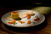 The Creme Brulee Cheesecake is served with an olive oil crisp and caramelized peaches at Fig & Olive in Newport Beach, CA.
