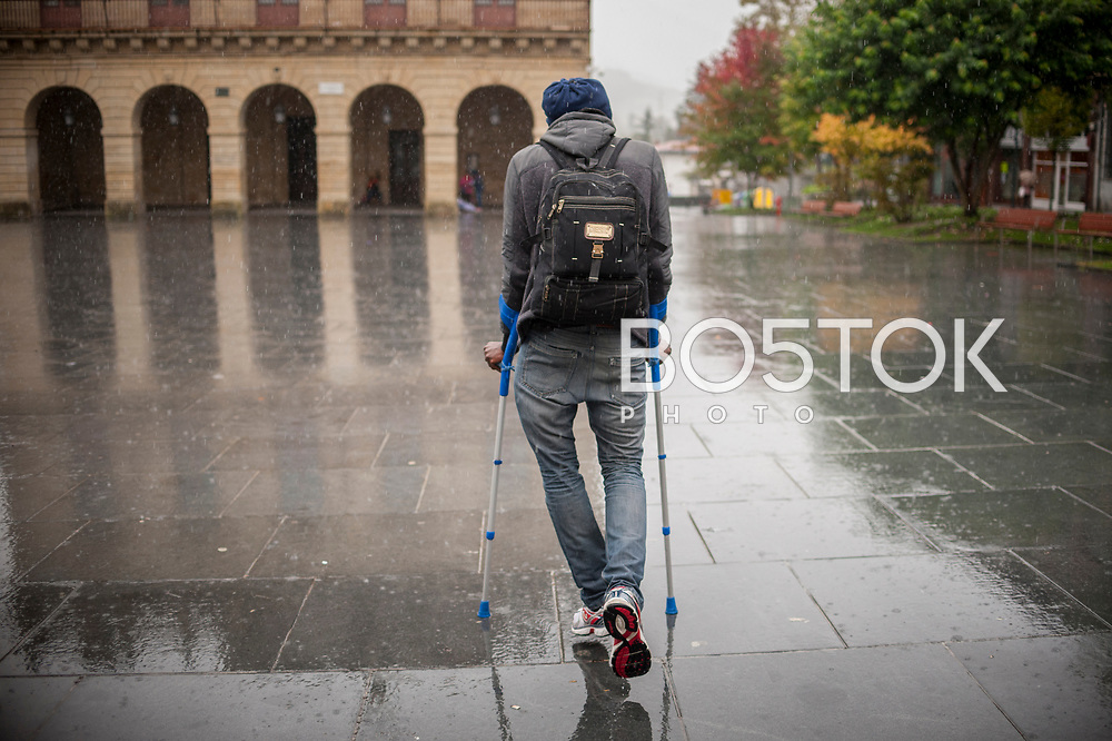 An African migrant with crutches walks under the rain. Irun (Basque Country). November 1, 2018. A group of volunteers has created a host network to serve migrants and inform about the public services they are entitled to and the ways to cross the border. This group of volunteers is avoiding a serious humanitarian problem Irun, the Basque municipality on the border with Hendaye. As the number of migrants arriving on the coasts of southern Spain incresead, more and more migrants are heading north to the border city of Irun. French authorities have reacted by conducting random checks as far as the city of Bordeaux, more than 200 kilometers north of the border. Migrants who are caught are then deported back to Irun. (Gari Garaialde / Bostok Photo).