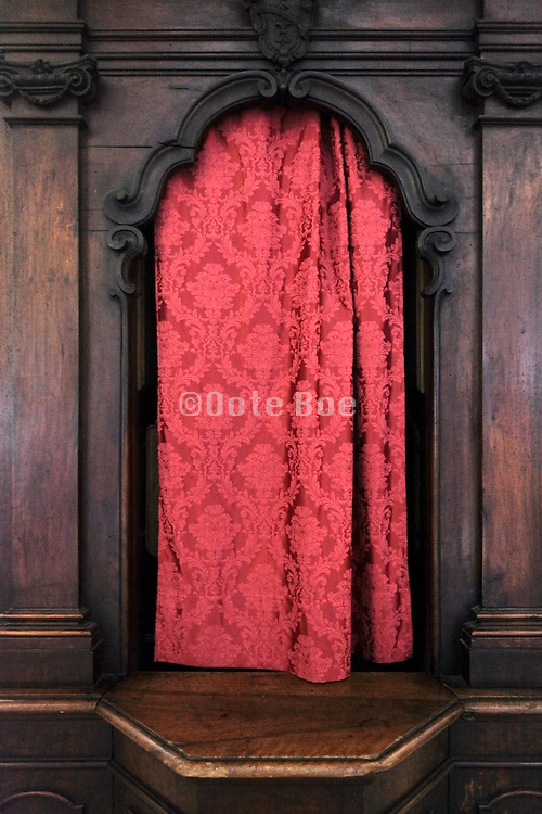 red curtain in a confession booth