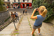 Young women taking a photo of cafes - Montmartre, Paris .<br /> <br /> Visit our FRANCE HISTORIC PLACES PHOTO COLLECTIONS for more photos to download or buy as wall art prints https://funkystock.photoshelter.com/gallery-collection/Pictures-Images-of-France-Photos-of-French-Historic-Landmark-Sites/C0000pDRcOaIqj8E