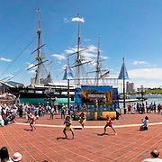 Outdoor performance of traditional Australian dancers at Harborplace in Baltimore Maryland, with city skyline and tall ship in the background. High resolution panorama.