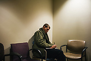 """BIRMINGHAM, AL – FEBRUARY 1, 2019:  Warren """"Azad"""" Stoddard, 24, completes paperwork at UAB Hospital-Highlands before receiving medical treatment for a gunshot wound he suffered while fighting ISIS alongside Kurdish YPG forces in Syria. CREDIT: Bob Miller for The New York Times<br /> <br /> In the war against ISIS, American volunteers have joined the ranks of a Syrian militia, operating independently of the United States. Until recently, the predominantly Kurdish YPG forces had enjoyed air and ground support from the United States, but now that US is officially leaving, the remaining American volunteers face uncertain odds. <br /> <br /> Warren Stoddard, 24, comes from a long line of military veterans and active service members. So when a knee injury prevented him from enlisting in the Marines in 2016, he reached out to a YPG liaison on Facebook to declare his interest in volunteering. """"I always wanted to serve, to do something worthwhile and to take part in some historical event,"""" Stoddard said. """"And I cared about the Kurdish cause."""" Two years later, as the Turkish invasion placed added pressure on the predominantly Kurdish YPG, Stoddard finally received an invitation to join and purchased his own one way ticket. Six months later, while engaging an ISIS stronghold alongside his YPG unit, Stoddard caught bullet fragments in his his upper thigh and foot, where a small fragment is still lodged."""