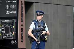 March 17, 2019 - Christchurch, New Zealand - An armed police officer stands guard outside the Christchurch District Court where the suspected shooter appeared in Christchurch on March 16, 2019. At least 49 people have died in the Christchurch mosque shooting, the worst terror attack in New Zealand history. The national security threat level has been increased from low to high for the first time in New Zealand's history after this attack. (Credit Image: © Sanka Vidanagama/NurPhoto via ZUMA Press)