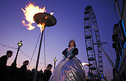 Months after the Millennium, a theatre group perform outside the London Aquarium on the Southbank and beneath a burning flame and the Millennium Wheel later to be renamed The London Eye, on 6th April 2000, on the Southbank, London, England.