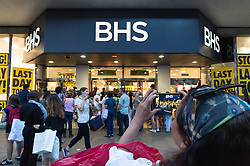© Licensed to London News Pictures. 13/08/2016. Woman takes a camera phone photo of  British Homes Stores Oxford Street Flagship store as it closes on its last day of trading. London, UK. Photo credit: Ray Tang/LNP