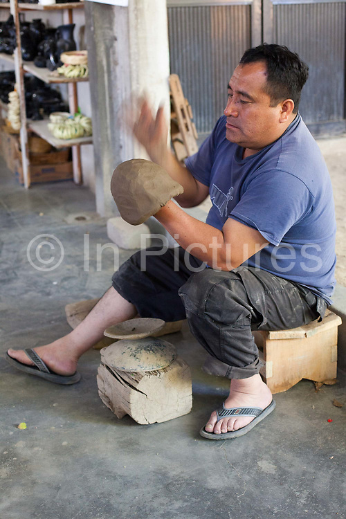 A potter at work making pottery in a Oaxacan pottery studio. Oaxaca in southern Mexico is known for its artisan communities, with each valley having a different specialism - weaving, pottery, wood carving.
