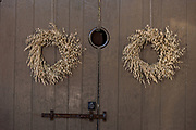 A wooden door on a historic home decorated with a Christmas wreath made from Sea Oats in Charleston, SC.