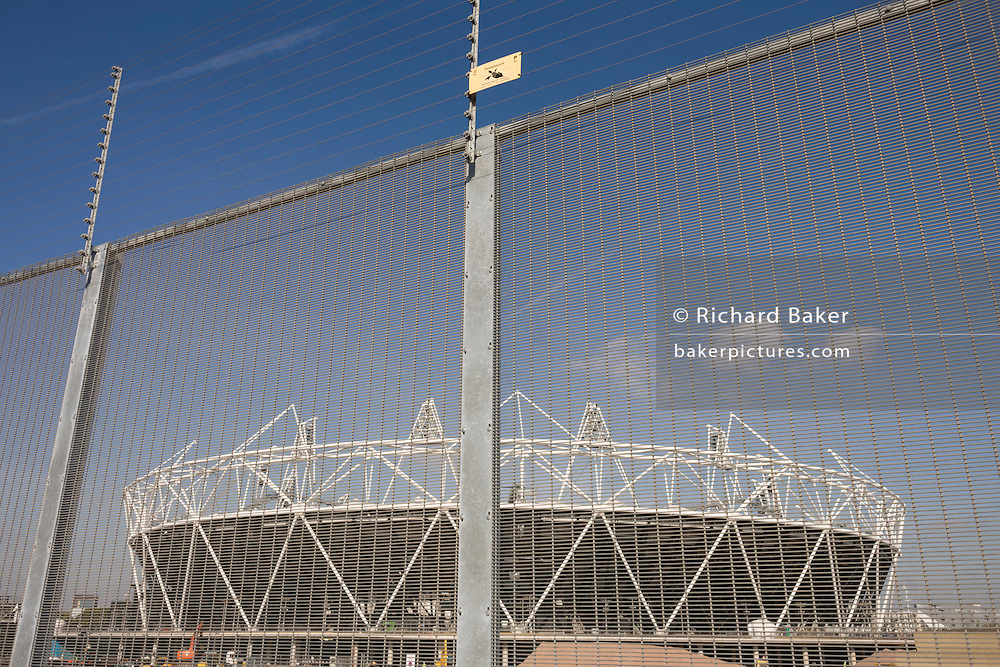The main stadium seen through the electrified perimeter fence at the 2012 Olympic Park in Stratford.