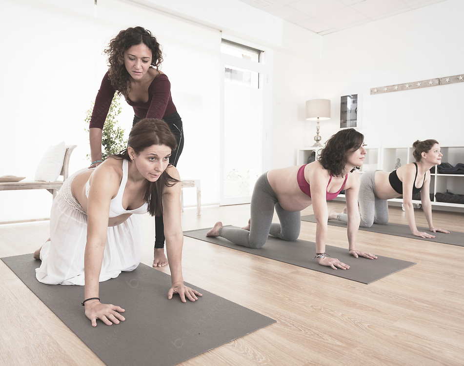 Instructor guiding correct movements in yoga class
