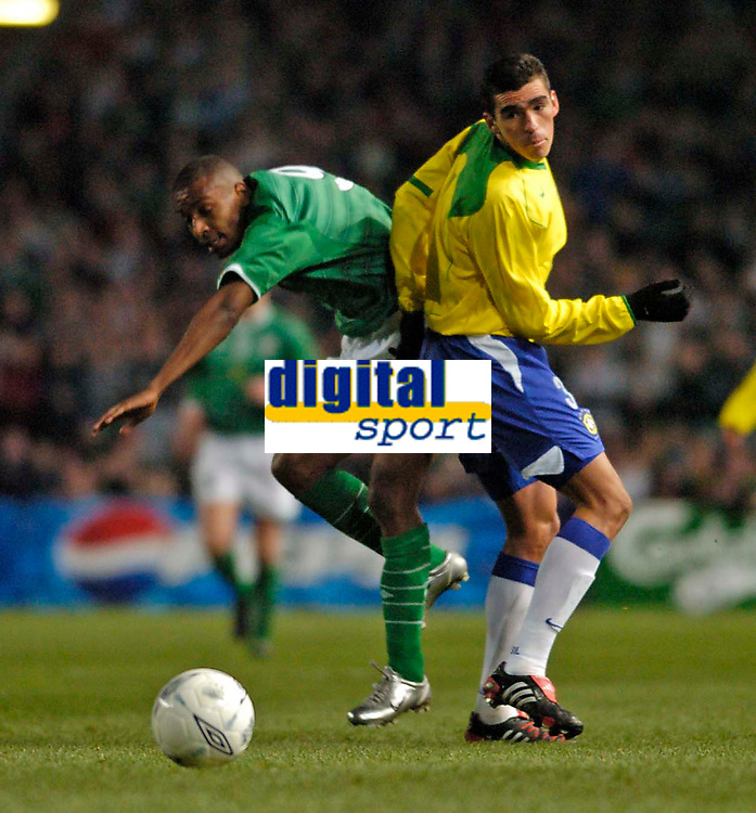 Photo. Jed Wee.<br /> Republic of Ireland v Brazil, International Friendly, Lansdowne Road, Dublin. 18/02/2004.<br /> Brazil's Lucio (R) watches Ireland's Clinton Morrison try to dart past him.