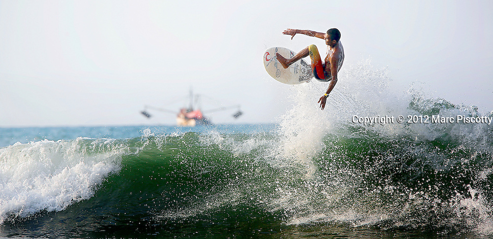 """SHOT 11/13/12 4:43:16 PM - A local surfer catches air off a wave one afternoon in Sayulita, Mexico. Sayulita is a small fishing village about 25 miles north of downtown Puerto Vallarta in the state of Nayarit, Mexico, with a population of approximately 4,000. Known for its consistent river mouth surf break, roving surfers """"discovered"""" Sayulita in the late 60's with the construction of Mexican Highway 200. In recent years, it has become increasingly popular as a holiday and vacation destination, especially with surfing enthusiasts and American and Canadian tourists. .(Photo by Marc Piscotty / © 2012)"""