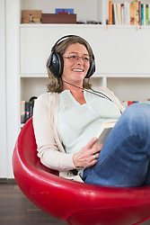 Mature woman sitting in armchair listening to music