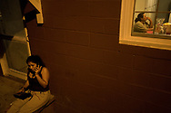 Carla Victoria Virgen, 30, of Nayarit, Mexico talks with family back home as Lus Cordero Yanez, 44, of Santiago, Mexico sits alone while eating dinner.