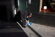 A businessman stoops to pick-up dropped paperwork that has spilled onto the pavement (sidewalk) in London.