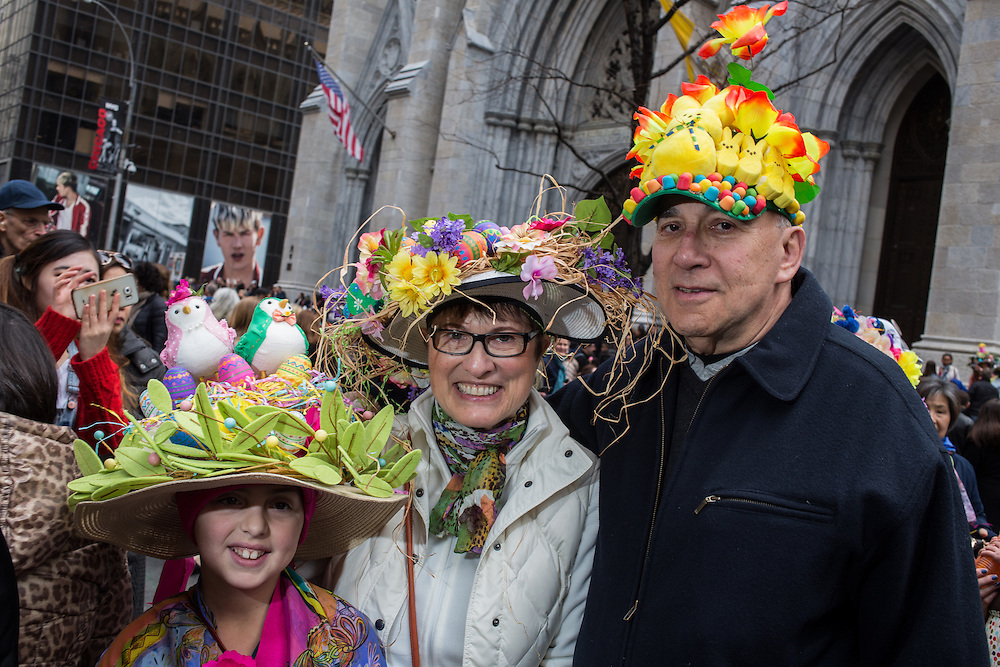 New York, NY, USA-27 March 2016. Gandparents with their granddaughter, all wearing colorful hats, in front of St. Patrick's Cathedral at the annual Easter Bonnet Parade and Festival
