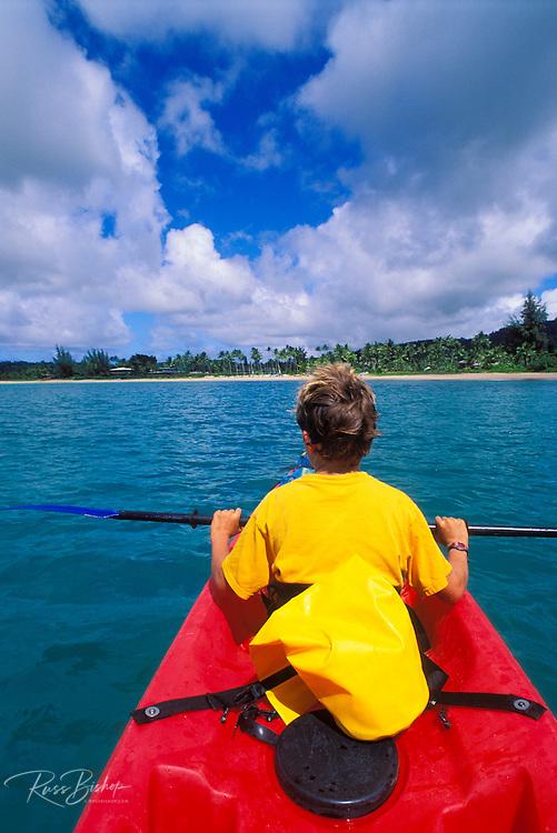 Boy kayaking on Hanalei Bay along the north shore, Island of Kauai, Hawaii
