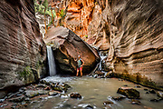 SHOT 8/7/17 1:26:05 PM - Vesta Lingvyte of Denver, Colorado pauses to take in the sights at Kanarraville Falls near Kanarraville, Utah. Kanarraville Falls is a hiking route through a narrow canyon with tree ladders and rope climbs leading to dramatic water cascades in a slot canyon. (Photo by Marc Piscotty / © 2017)