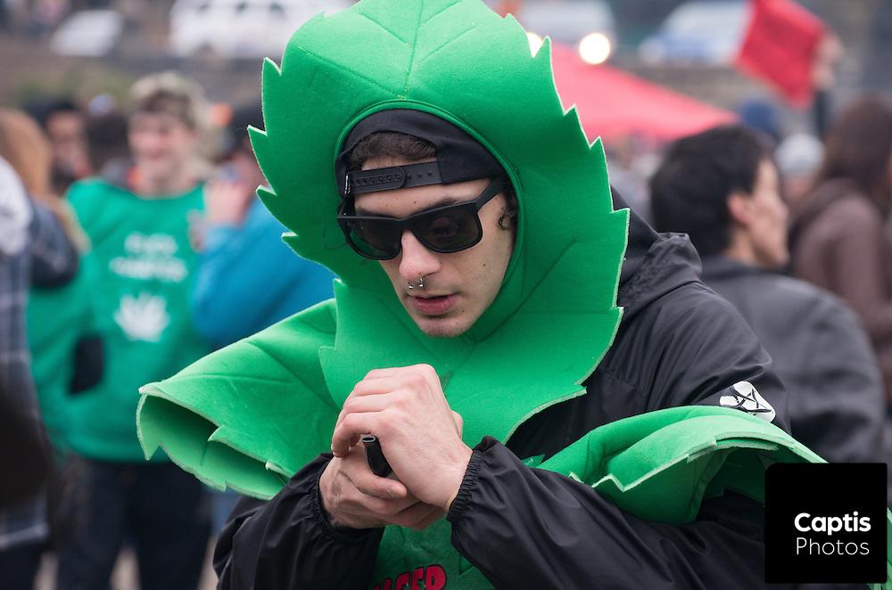 A man dressed as a cannabis leaf smokes. April 20, 2015