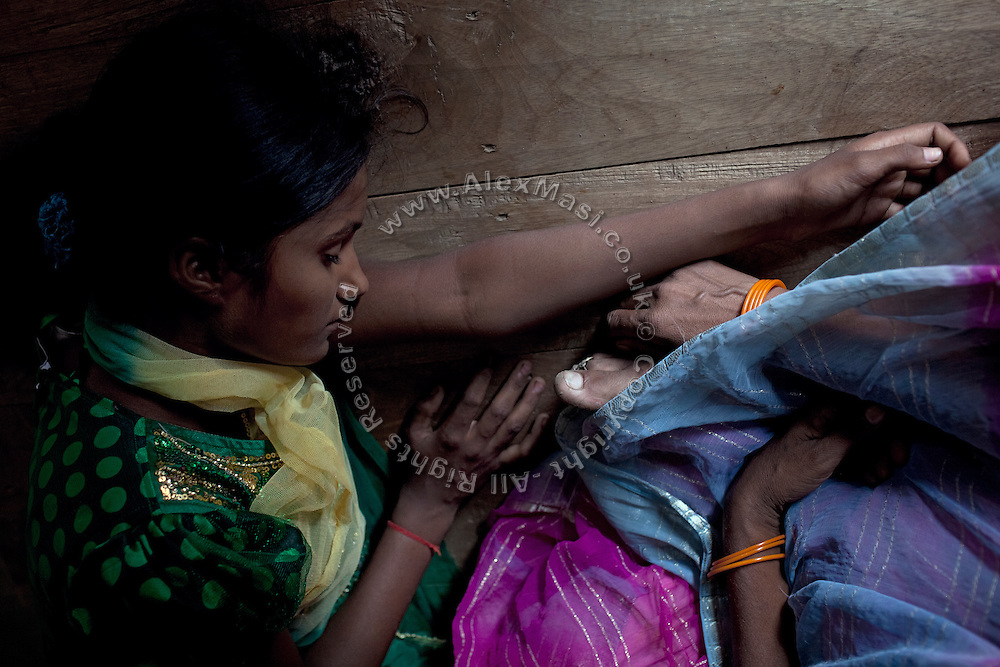 (name changed) Kanchan Kumari Sharma, 12, sick with fever, is lying next to her mother, Malti Devi, 40, inside their home in Sersiya Kekrahi village, Varanasi District, Uttar Pradesh, India. In 2012, Kanchan went with a friend to bring lunch to her father, around 2 km away from her home. On the way they met Rajesh (rapist) and Ashok, a friend of his. Both girls were picked up on the spot using an excuse. Ashok drove Kanchan's friend home, but Rajesh forced Kanchan to travel with him during six days and for hundreds of kilometres across different states. (Mirzapur / Chennai / Itarsi / Bhusawal) He raped her once behind the station in Itarsi. With great effort and some coincidence, the uncle of Kanchan managed to bring her back home. Although she was scared, she insisted on going to the police to file a case (FIR). She was kept at the police station for 12 days and threatened to prevent her from filing an official case. Ashok and Rajesh are from higher caste and wealthy families. While Rajesh spent 24 days in jail initially in summer 2012, he is now a free man while the trial is still going on. Kanchan's family is now struggling to put together 30.000 Indian Rupees (500 USD) to continue battling for justice in court.