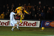 Newport's Christian Jolley skips over the tackle from Wimbledon's Alan Bennett. Skybet football league 2, Newport county v AFC Wimbledon match at Rodney Parade in Newport, South Wales on Tuesday 25th Feb 2014.<br /> pic by Andrew Orchard, Andrew Orchard sports photography.
