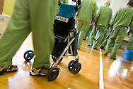 Following a roll call of names, elderly prisoners (and one pushing a stroller chair for stability) make their way to a room for their lunch,  in Onomichi prison, Japan. Monday, May 19th, 2008