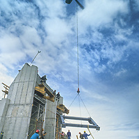 A huge Sikorsky Skycrane helicopter lowers prefabricated steel beam structures into place for a new tram station atop 11,166-foot Lone Mountain at Montana's Big Sky Ski Area.