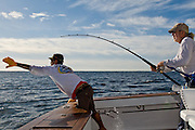 Stand up light tackle angler working with mate to get release.