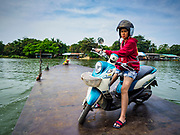 "09 JANUARY 2019 - KANCHANABURI, THAILAND: A woman riding a small ferry across the River Kwai takes off her motorcycle helmet. The ferry goes across the River Kwai downriver from downtown Kanchanaburi, the site of the famous ""Bridge on the River Kwai."" Small ferries like this, once common on Thai river crossings, are disappearing because Thailand has dramatically improved its infrastructure since this ferry started operating about 50 years ago. The ferry operator said his grandfather started the ferry, with a small raft he would pole across the river, in the late 1960s. Now his family has a metal boat with an inboard engine. There are large vehicle bridges across the river about 5 miles north and south of this ferry crossing, but for people in rural communities on the west side of the river the ferry is still the most convenient way to cross the river.      PHOTO BY JACK KURTZ"