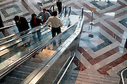 workers on escalators going up or stepping off to lobby