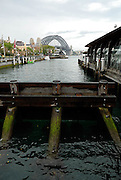 Timber safety-barriers for the Sydney Harbour Ferries, with the Sydney Harbour Bridge in the background. Circular Quay, Sydney, Australia