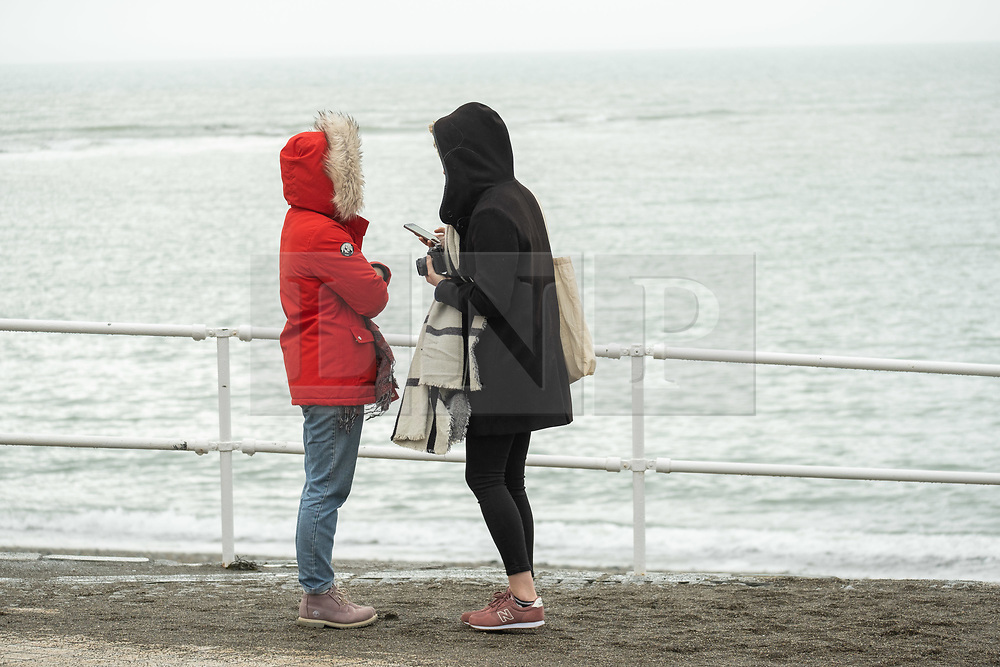 © Licensed to London News Pictures. Aberystwyth Wales UK, 28/02/2019.<br />  On the last day of meteorological winter, people in their rain-clothes, walk along the seafront in Aberystwyth on a grey,  cold and damp day , in sharp contrast to the recent record breaking heat and sunshine, and much more  typical windy and cooler conditions to be expected at the end of February and beginning of March<br /> Photo credit Keith Morris / LNP