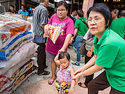"""07 AUGUST 2014 - BANGKOK, THAILAND:  A woman and her child carries a sack of rice away from a food distribution at Pek Leng Keng Mangkorn Khiew Shrine in Bangkok. Thousands of people lined up for food distribution at the Pek Leng Keng Mangkorn Khiew Shrine in the Khlong Toei section of Bangkok Thursday. Khlong Toei is one of the poorest sections of Bangkok. The seventh month of the Chinese Lunar calendar is called """"Ghost Month"""" during which ghosts and spirits, including those of the deceased ancestors, come out from the lower realm. It is common for Chinese people to make merit during the month by burning """"hell money"""" and presenting food to the ghosts. At Chinese temples in Thailand, it is also customary to give food to the poorer people in the community.       PHOTO BY JACK KURTZ"""
