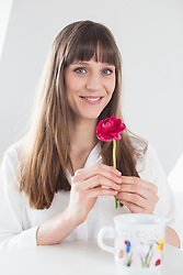 Portrait of woman with single pink flower, smiling