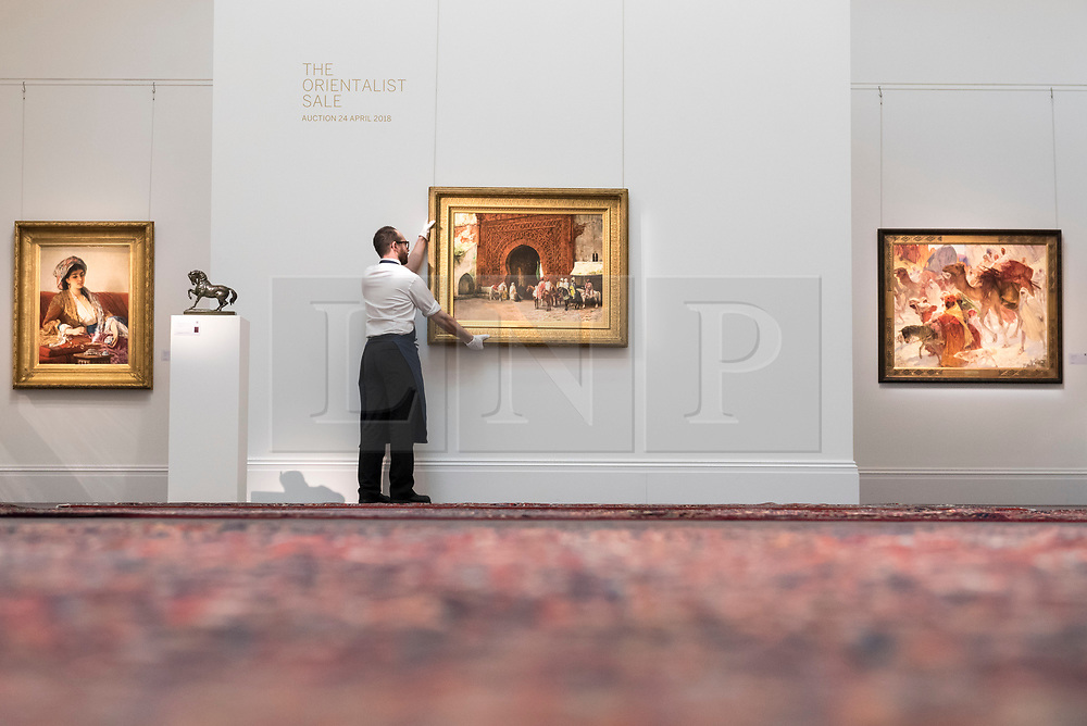 """© Licensed to London News Pictures. 20/04/2018. LONDON, UK. A technician presents (C) """"Rabat (The Red Gate)"""" by Edwin Lord Weeks (Est. GBP200-300k), amongst other works at a preview of works in Sotheby's 20th Century Middle East, Orientalist and Islamic upcoming art sales in New Bond Street.  The works will be sold at auction in the last week of April.    Photo credit: Stephen Chung/LNP"""