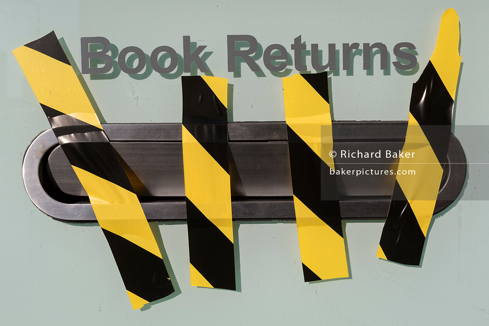 As the number of UK Coronavirus cases rose to over 8,000, it was announced that thousands of 15-minute home tests could be made available within days to those self-isolating with symptoms, hazard tape blocks the book returns slot at a closed Southwark library in Borough, on 25th March 2020, in London, England.
