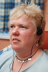 Woman with visual impairment using headphones.