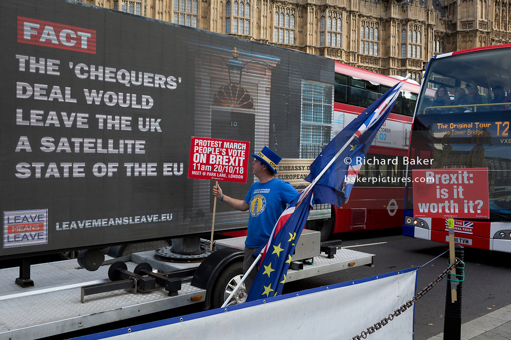 A pro-Europe anti-Brexit protester stands next to a mobile pro-Leave ad travelling around the capital's streets, opposite the British Houses of Parliament in Westminster, on 16th October 2018, in London, England.