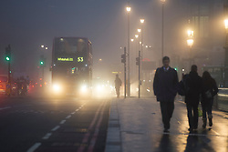 © London News Pictures. 11/12/2013. London, UK.  Traffic and commuters cross Westminster bridge, covered in fog early morning in central London on December 11, 2013. Photo credit: Ben Cawthra/LNP