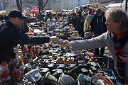 Euros changing hands for bric-a-brac and old possessions, sold at a giant market in Mauerpark - an open space on the site of the old Berlin wall, the former border between Communist East and West Berlin during the Cold War. The flea market is visited by tourists and local Berliners and tourists alike, taking place every Sunday on Bernauer Strasse where the wall turned sharp left and cut through where stallholders now offer their wares.