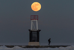 © Licensed to London News Pictures. 01/01/2018. CHICAGO, USA. A man walks across the jetty at the ice covered North Avenue beach as the supermoon rises on one of the coldest New Year's Days in decades.  The moon is at its closest point, the perigee, to Earth during its monthly orbit and appears 30% brighter and 14% larger.  January 2018 sees a supermoon known as a 'wolf moon' on 1 January and a 'blue moon' on 31 January.  Photo credit: Stephen Chung/LNP