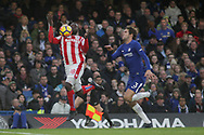 Mame Biram Diouf of Stoke city controls the ball under pressure from Marcos Alonso of Chelsea and 'scores' a goal but sees it ruled out after he had handled the ball.<br /> Premier league match, Chelsea v Stoke city at Stamford Bridge in London on Saturday 30th December 2017.<br /> pic by Kieran Clarke, Andrew Orchard sports photography.