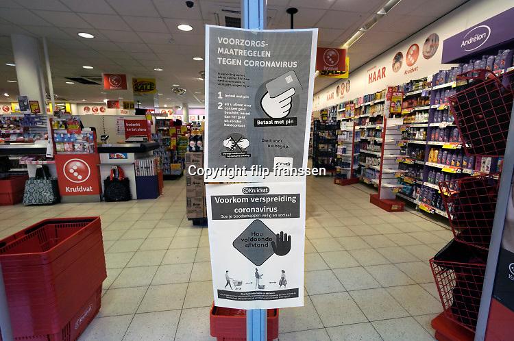 Nederland, Nijmegen, 16-3-2020 In de winkelstraten is het een stuk rustiger als normaal . Veel winkels hebben bij de ingang een mededeling die verwijst naar het handen schudden of afstand houden van het personeel naar de klant toe . Er wordt bij het Kruidvat gevraagd met pin of contactloos te betalen pinnen . Foto: Flip Franssen