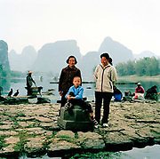 Liu Tong, 5 is pictured on the banks of the River Li, near Fulli Town Village, Guangxi province, where he lives with his grandmother, Wang Li Hua, 82, left, and his mother, Zhao Juan, 35. His grandmother still works on the family farm and his mother works in the tourist industry.The day we took this picture was the first day his grand mother had been on a boat and Tong's first ever day in the town of Yangshuo across the river from where they live. ..Its over thirty years (1978) since the Mao's Chinese government brought in the One Child Policy in a bid to control the world's biggest, growing population. It has been successful, in controlling growth, but has led to other problems. E.G. a gender in-balance with a projected 30 million to many boys babies; Labour shortages and a lack of care for the elderly.