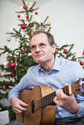 Mature man playing guitar against Christmas tree