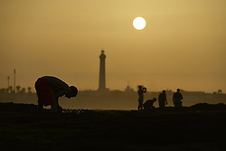June 25, 2017 - Casablanca, Morocco - A man washes his face on a rocky beach during a nice sunset near Hassan II mosque in Casablanca hours only from the start of Eid Al Fitr celebrations. The holy feast of Eid Al Fitr in Morocco will be celebrated from Monday morning.  (Credit Image: © Artur Widak/NurPhoto via ZUMA Press)