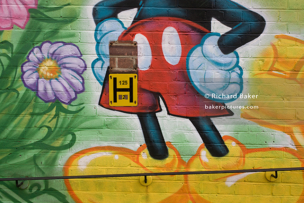 A Disney Mickey Mouse street mural on the front wall of a Southwark nursery in London, England. Sprayed with aerosol on the brickwork and incorporating the rail of a ramp for parents to enter the building and the sign attached that tells firemen where the nearrest water hydrant is located in the event of emergency. Mickey Mouse is a funny animal cartoon character created in 1928 by Walt Disney and Ub Iwerks at the Walt Disney Studios. Mickey is an anthropomorphic mouse, the official mascot of The Walt Disney Company and one of the most recognizable cartoon characters in the world.