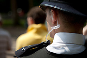 Police officer with communications ear piece during heavily policed event in London.