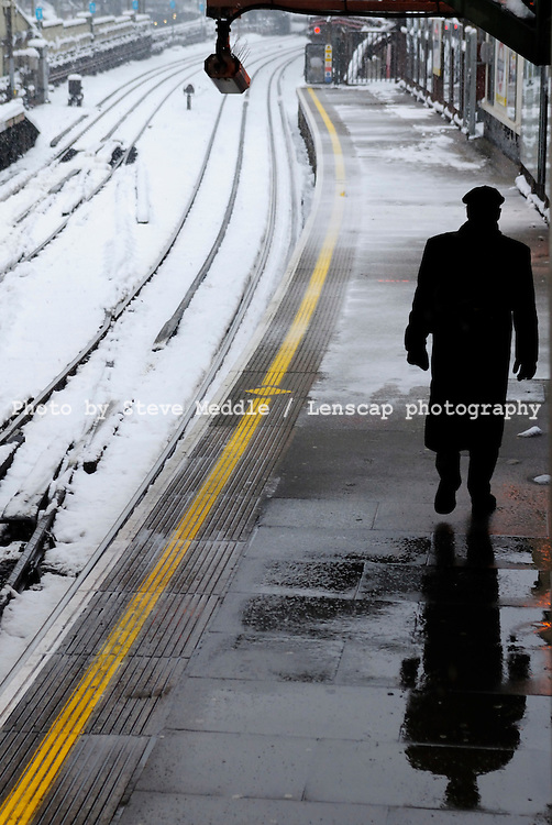 Commuter waiting for an underground train to arrive at Farringdon Tube Station during