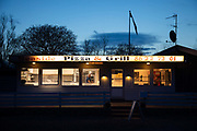 The owner of a pizza and grill bar waiting for costumers at dusk on a Saturday night on April 4th 2020 in Skaering, Denmark. It is two weeks into the Danish corona lock-down and business is slow on a Saturday night in the small community Skæring.