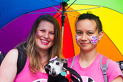 London, June 28th 2014. Two women shelter from the rain as the Pride London parade proceeds through the city's streets.